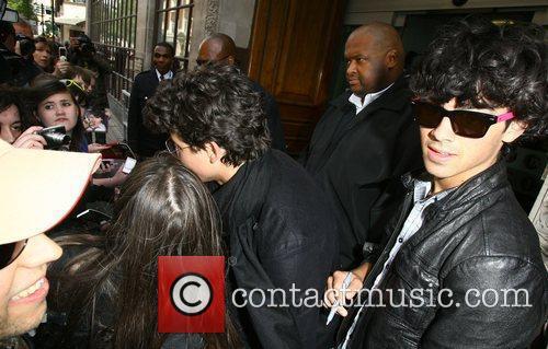 Nick Jonas and Joe Jonas  are surrounded...