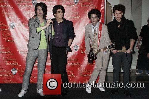 Joe Jonas and Nick Jonas pose with their...