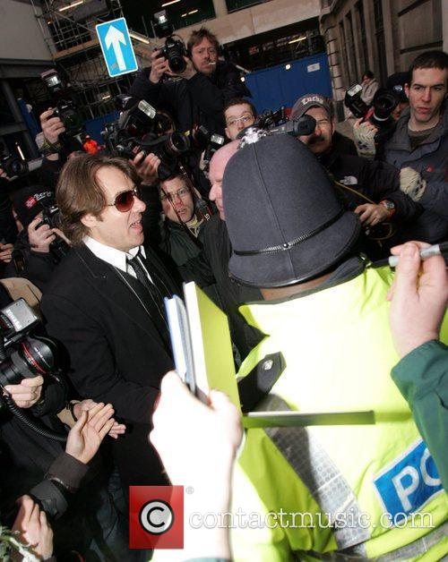 Jonathan Ross is surrounded by photographers and police...