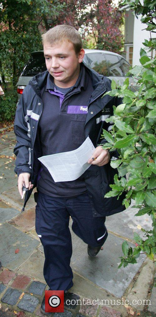 A FedEx courier collects a package from the...