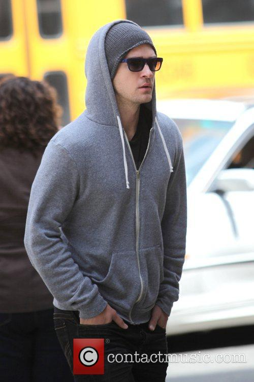 Justin Timberlake wearing a grey hoodie and sunglasses...