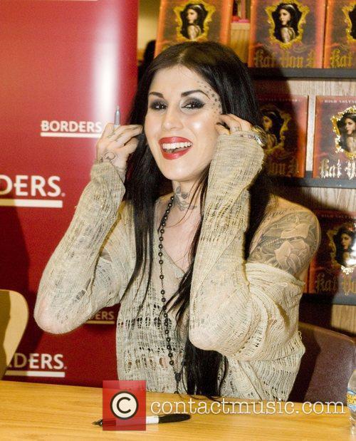 Tattoo artist Kat Von D signs copies of...