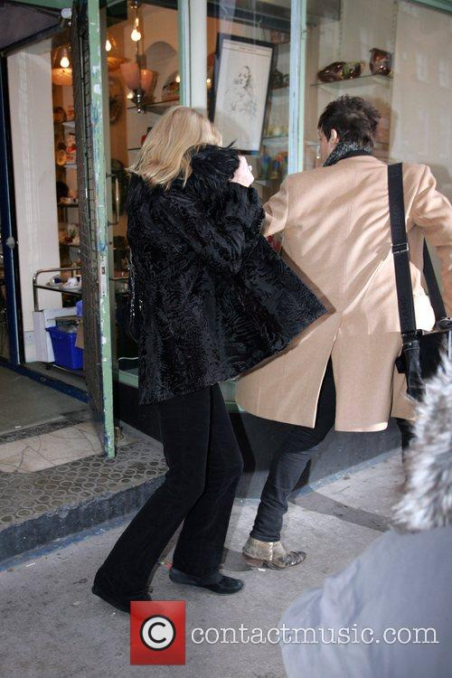 Kate Moss shields herself from photographers as she...