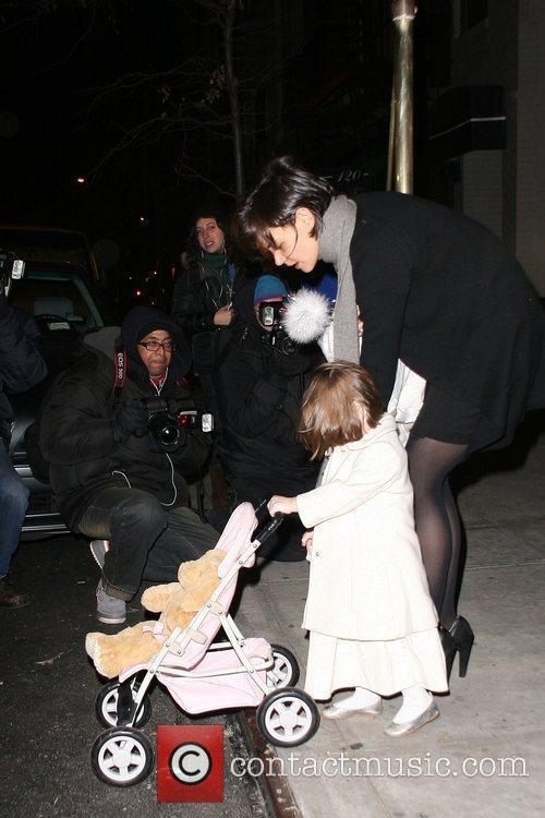 Suri Cruise pushes her baby carriage with her...