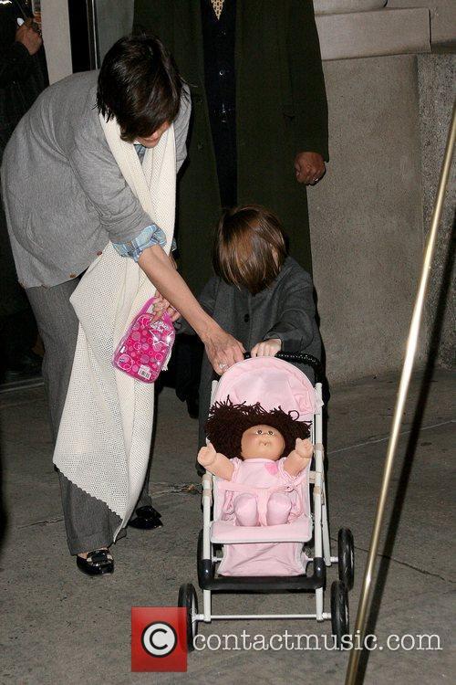 Katie Holmes helps her daughter Suri push a...