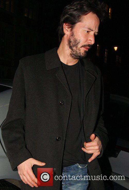 Keanu Reeves arriving at his hotel wearing old...