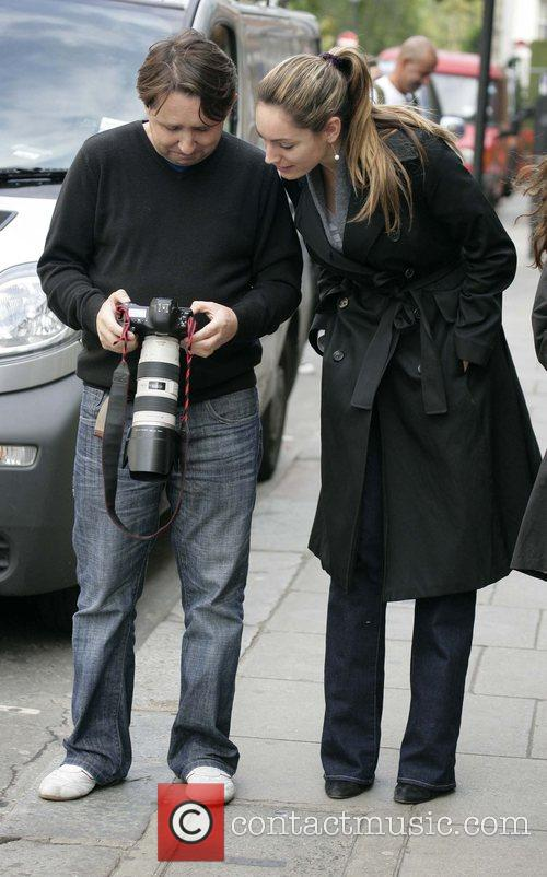 Kelly Brook checks out a photogapher's pictures of...