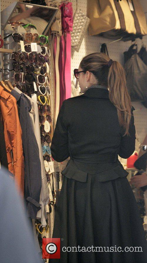 Kelly Brook tries on sunglasses during a shopping...