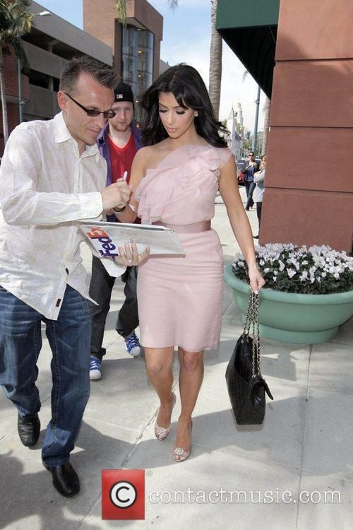 Kim Kardashian  signs an autograph on her...