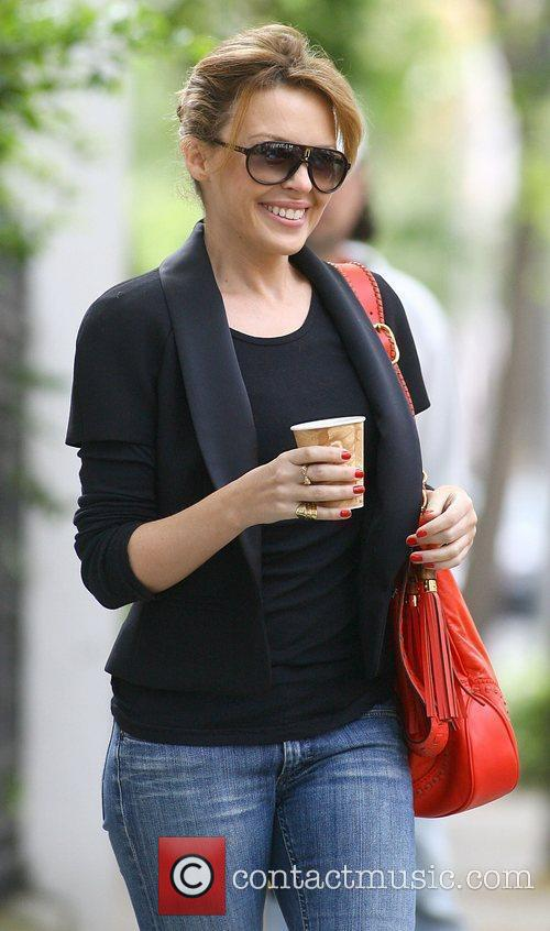 Carries a coffee as she leaves her home...