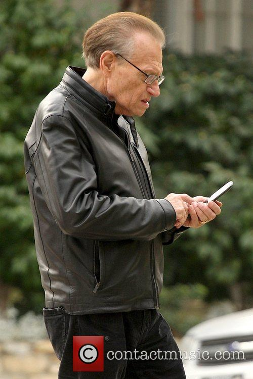 Larry King talking on his cell phone while...