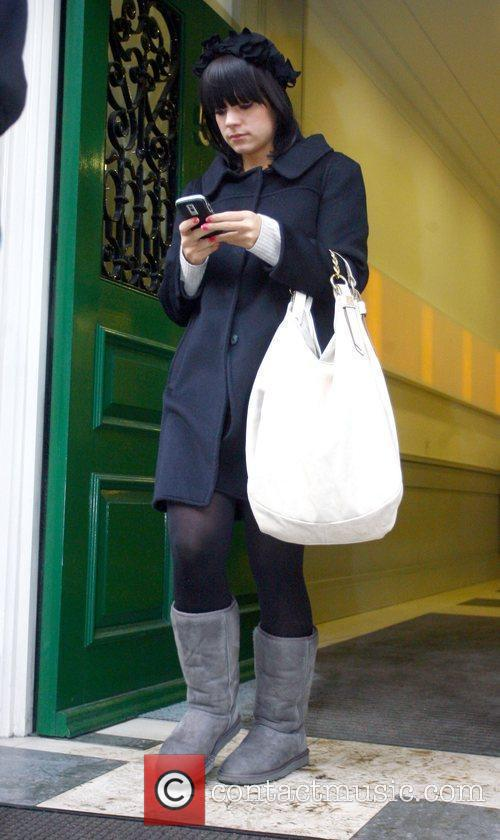 Lily Allen checks her mobile phone while out...