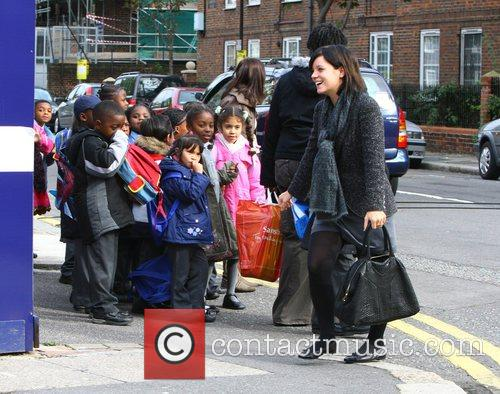 Lily Allen waves at a group of school...