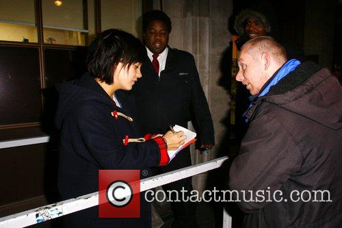 Lily Allen signs an autograph for a waiting...