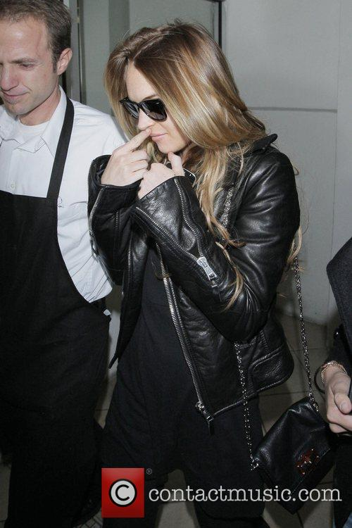 Lindsay Lohan tries to hide her face from...