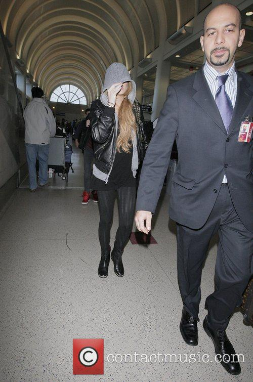 Lindsay Lohan covering her face with her hood...