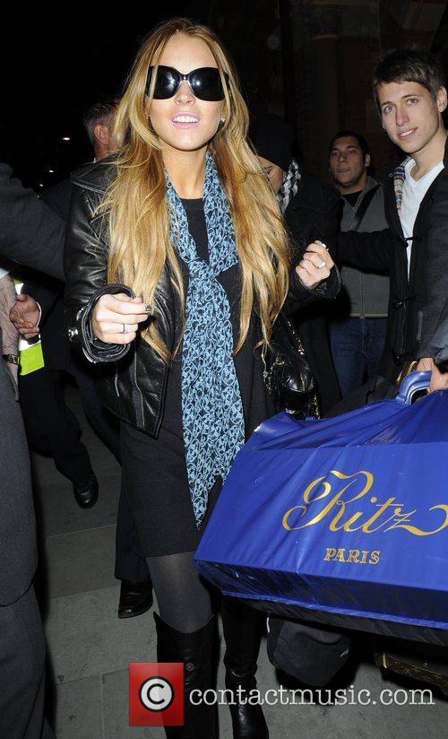 Lindsay Lohan is escorted by police upon returning...