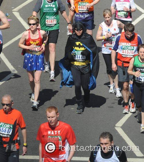 A man dressed as Batman runs along the...