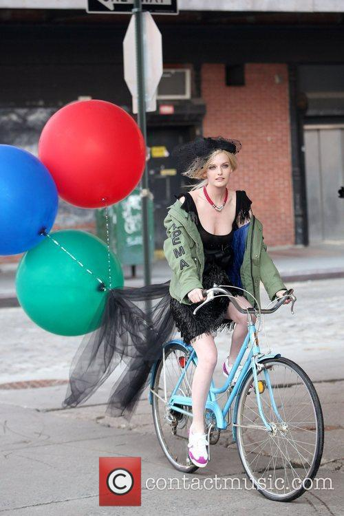 Rides a bicycle during a fashion shoot in...
