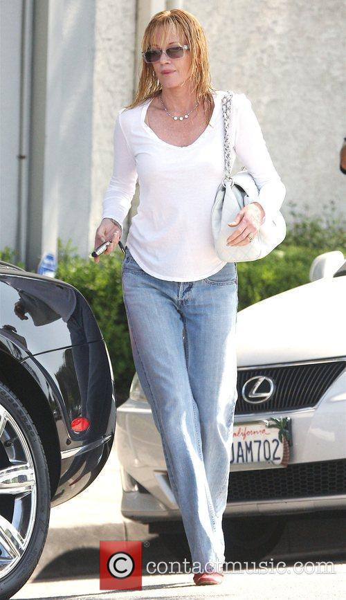 Melanie Griffith, carrying a white Chanel handbag, leaves...