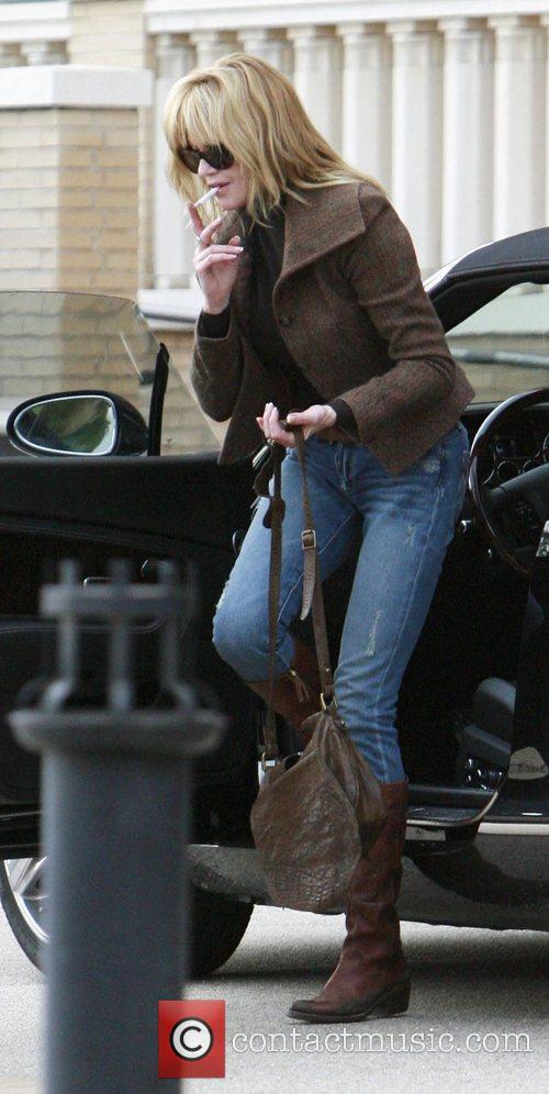 Melanie Griffith smokes a cigarette as she steps...