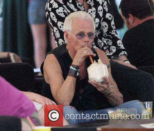 Drinks from a coconut while relaxing at Coachella...