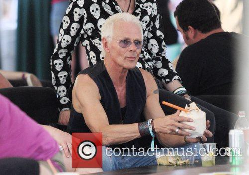 Michael Des Barres drinks from a coconut while...