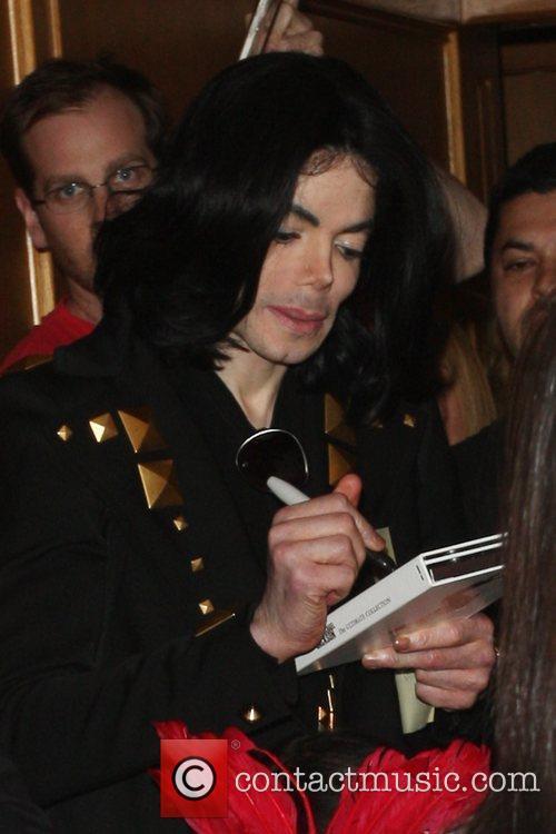 Michael Jackson  signs an autograph as he...