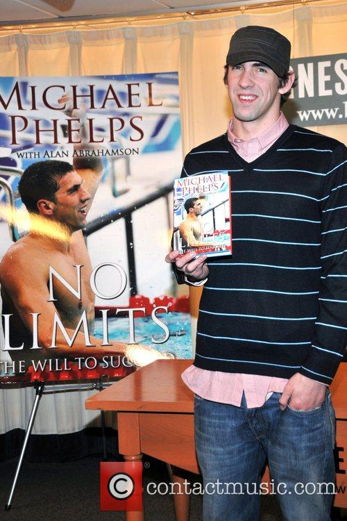 Signs copies of his book 'No Limits: The...