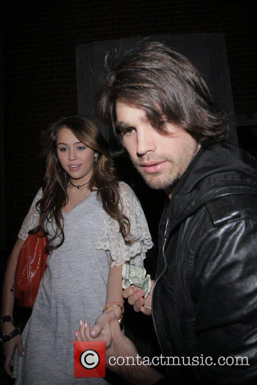 Miley Cyrus and her boyfriend Justin Gaston leaving...