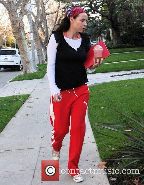Minnie Driver, wearing red Puma sweat pants, returning...
