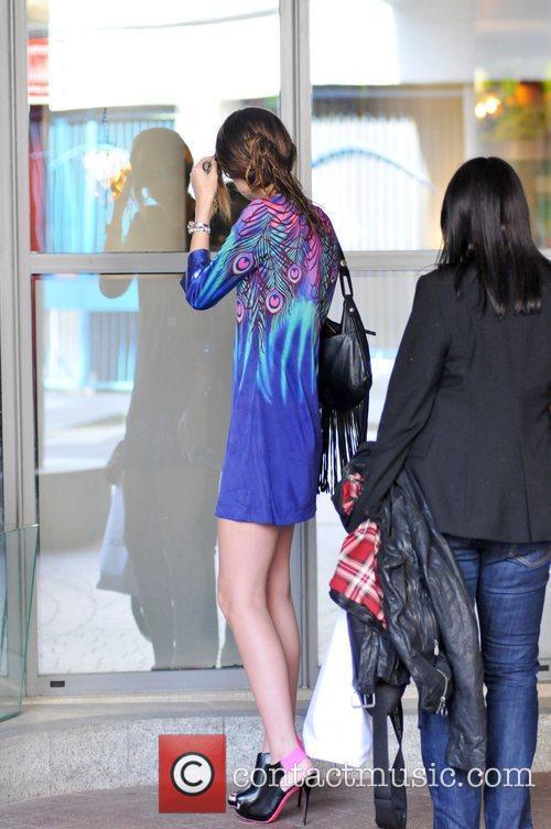Mischa Barton checks herself in a window outside...