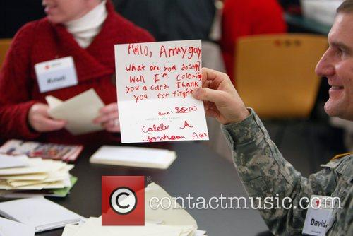 A solider reads a card during the Holiday...