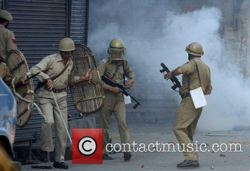 Kashmiri Muslims throw stones during a protest against...