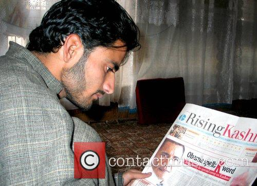 A Kashmiri man looks through the newspaper featuring...