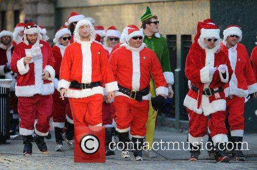Santas participating in Manhattan's 2008 SantaCon walking along...