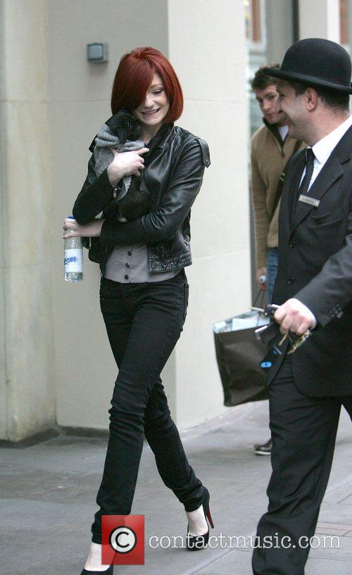 Carrying her puppy outside her hotel