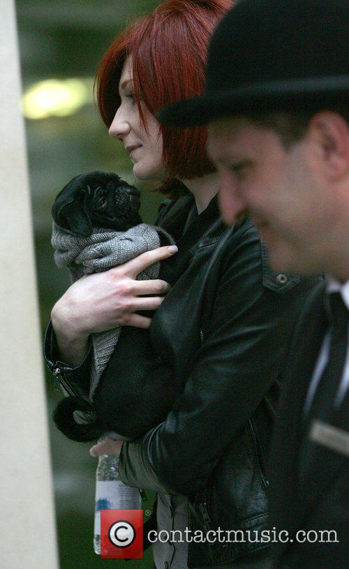 Nicola Roberts of Girls Aloud carrying her puppy...