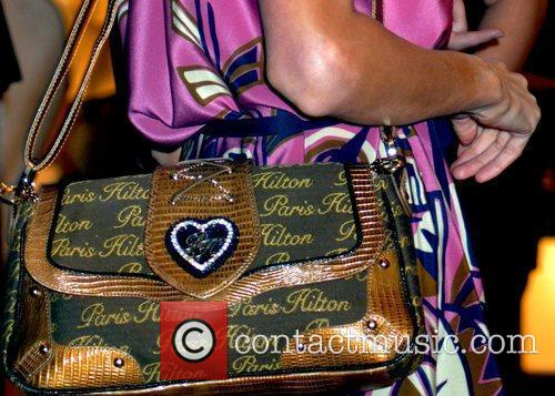 Carrying one of her own Paris Hilton handbags...