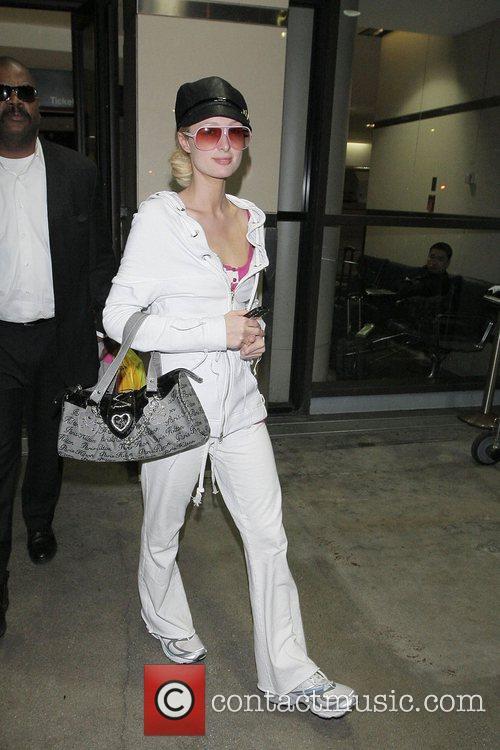 Paris Hilton, wearing no makeup and white sweatsuit,...