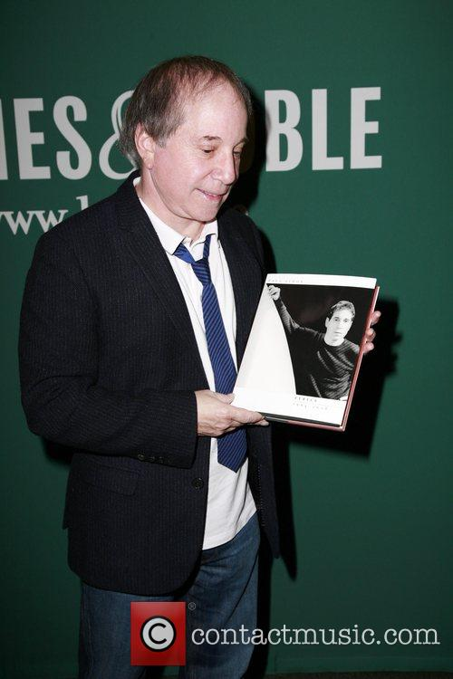 Signs copies of his book Paul Simon: Lyrics...