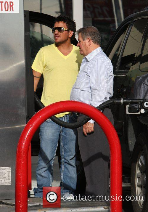 Peter Andre with his father filling up the...