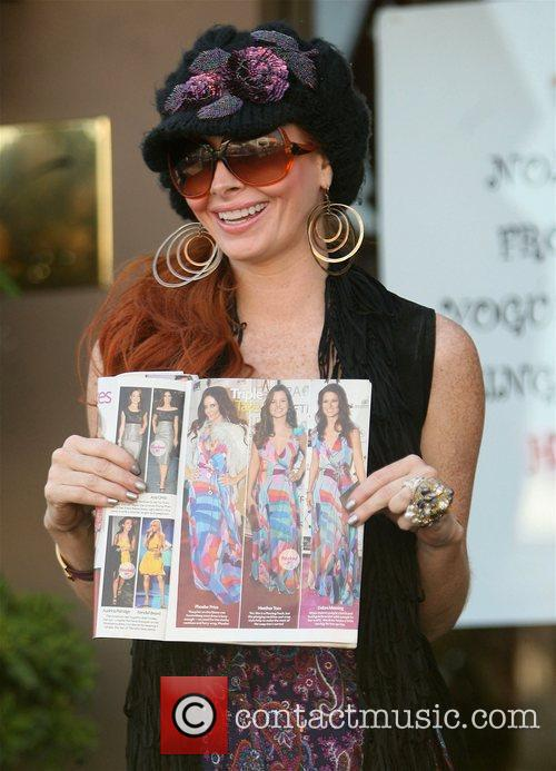 Phoebe Price holding a magazine featuring a picture...