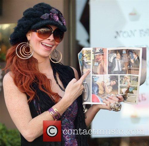 Holding a magazine featuring a picture of herself