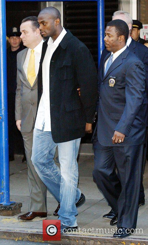 New York Giants Plaxico Burress Is In Handcuffs As He Is Led Out Of The Manhattan's 17th Precinct For Criminal Possession Of A Weapon 4