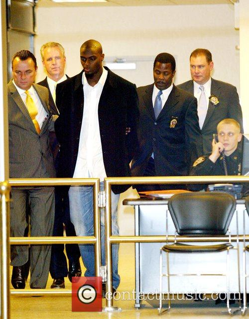 New York Giants Plaxico Burress Is In Handcuffs As He Is Led Out Of The Manhattan's 17th Precinct For Criminal Possession Of A Weapon 8