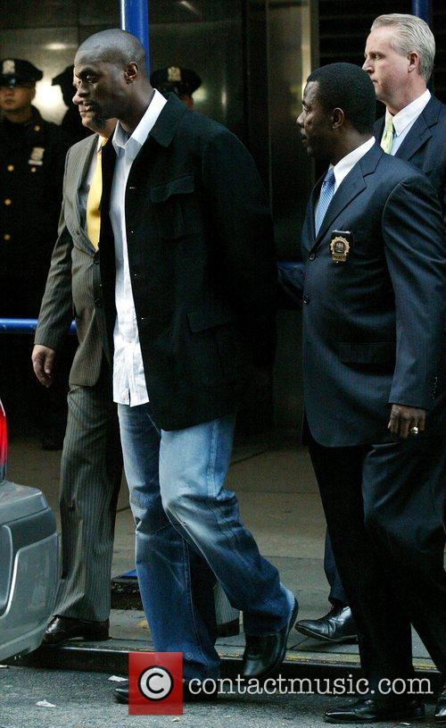 New York Giants Plaxico Burress Is In Handcuffs As He Is Led Out Of The Manhattan's 17th Precinct For Criminal Possession Of A Weapon 3