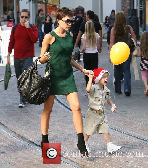 Victoria Beckham wearing a little green dress and...