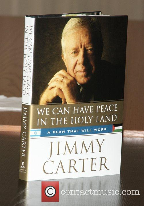 Former President Jimmy Carter signs copies of his...