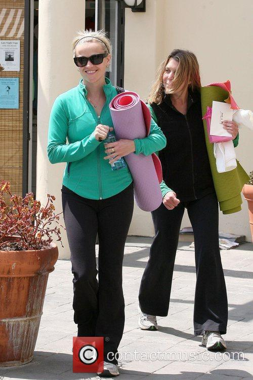 Reese Witherspoon carrying a yoga mat while leaving...